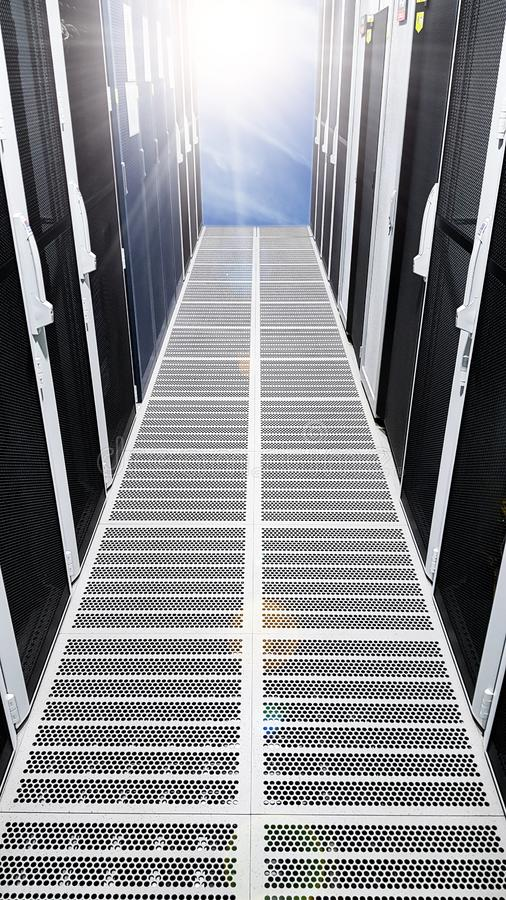 Modern big data server room corridor hallway with high racks full of network servers and storage blades and sun light at the end royalty free stock photography