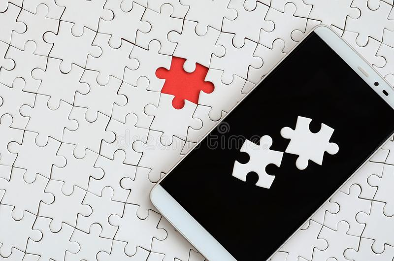 A modern big smartphone with several puzzle elements on the touch screen lies on a white jigsaw puzzle in an assembled state with. Missing elements stock photos
