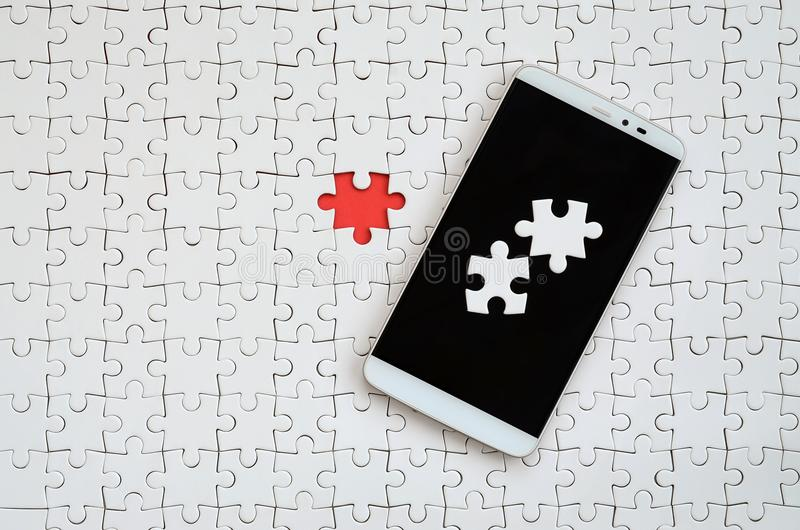 A modern big smartphone with several puzzle elements on the touch screen lies on a white jigsaw puzzle in an assembled state with. Missing elements royalty free stock images
