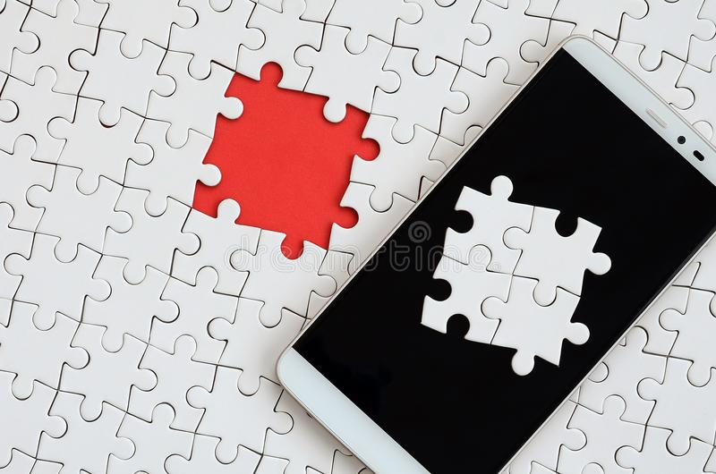 A modern big smartphone with several puzzle elements on the touch screen lies on a white jigsaw puzzle in an assembled state with. Missing elements royalty free stock photo