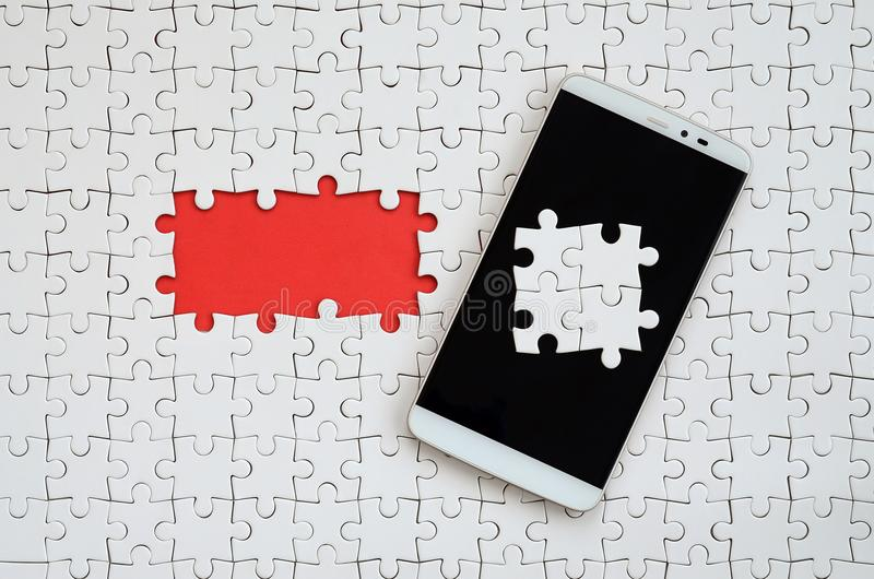 A modern big smartphone with several puzzle elements on the touch screen lies on a white jigsaw puzzle in an assembled state with. Missing elements royalty free stock photos