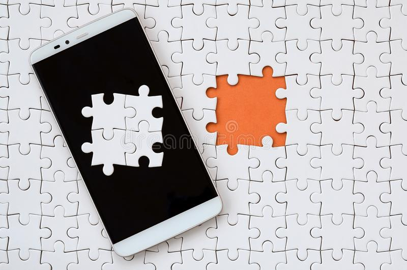 A modern big smartphone with several puzzle elements on the touch screen lies on a white jigsaw puzzle in an assembled state with. Missing elements stock photo