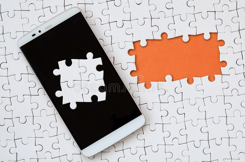 A modern big smartphone with several puzzle elements on the touch screen lies on a white jigsaw puzzle in an assembled state with. Missing elements stock illustration