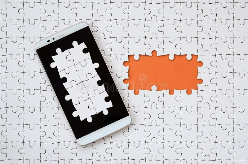 A modern big smartphone with several puzzle elements on the touch screen lies on a white jigsaw puzzle in an assembled state with. Missing elements royalty free illustration