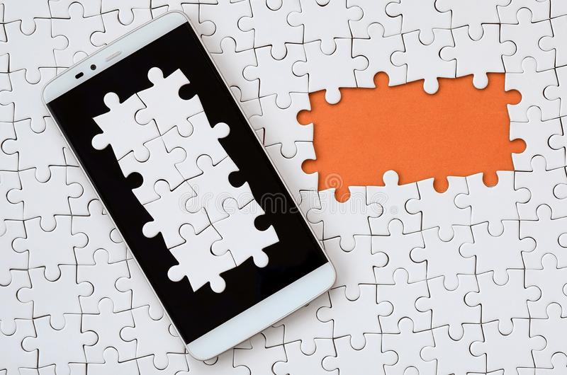 A modern big smartphone with several puzzle elements on the touch screen lies on a white jigsaw puzzle in an assembled state with. Missing elements stock images