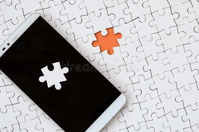 A modern big smartphone with several puzzle elements on the touch screen lies on a white jigsaw puzzle in an assembled state with. Missing elements stock image