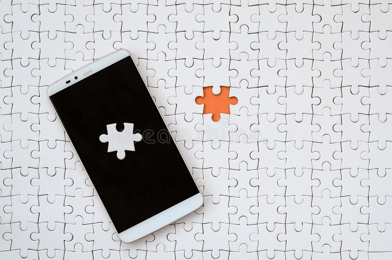 A modern big smartphone with several puzzle elements on the touch screen lies on a white jigsaw puzzle in an assembled state with. Missing elements royalty free stock image