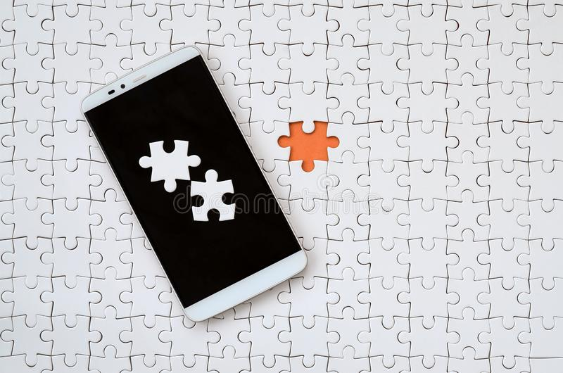A modern big smartphone with several puzzle elements on the touch screen lies on a white jigsaw puzzle in an assembled state with. Missing elements royalty free stock photography