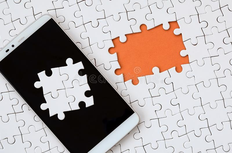 A modern big smartphone with several puzzle elements on the touch screen lies on a white jigsaw puzzle in an assembled state with. Missing elements stock photography