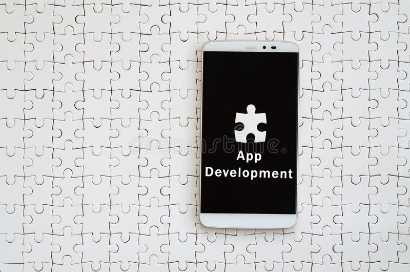 A modern big smartphone with a touch screen lies on a white jigs. Aw puzzle in an assembled state with inscription. App development royalty free stock photo