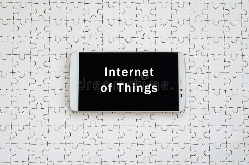 A modern big smartphone with a touch screen lies on a white jigs. Aw puzzle in an assembled state with inscription. Internet of Things royalty free stock photo