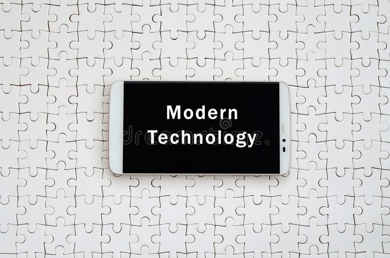 A modern big smartphone with a touch screen lies on a white jigs. Aw puzzle in an assembled state with inscription. Modern technology stock image
