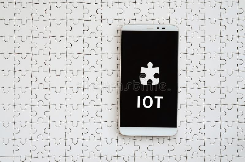 A modern big smartphone with a touch screen lies on a white jigs. Aw puzzle in an assembled state with inscription. IOT stock photos