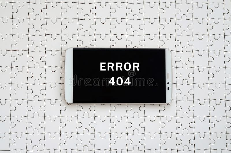 A modern big smartphone with a touch screen lies on a white jigs. Aw puzzle in an assembled state with inscription. Error 404 stock images