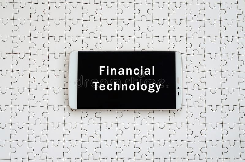 A modern big smartphone with a touch screen lies on a white jigs. Aw puzzle in an assembled state with inscription. Financial technology royalty free stock image
