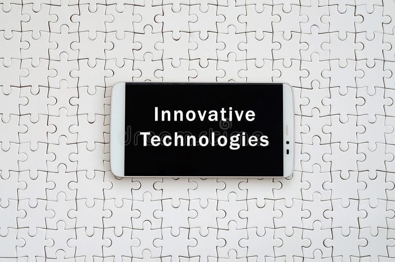 A modern big smartphone with a touch screen lies on a white jigs. Aw puzzle in an assembled state with inscription. Innovative technologies stock photo
