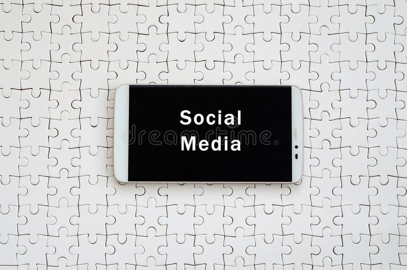 A modern big smartphone with a touch screen lies on a white jigs. Aw puzzle in an assembled state with inscription. Social media stock photos