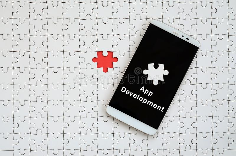 A modern big smartphone with a touch screen lies on a white jigs. Aw puzzle in an assembled state with inscription. App development stock photo