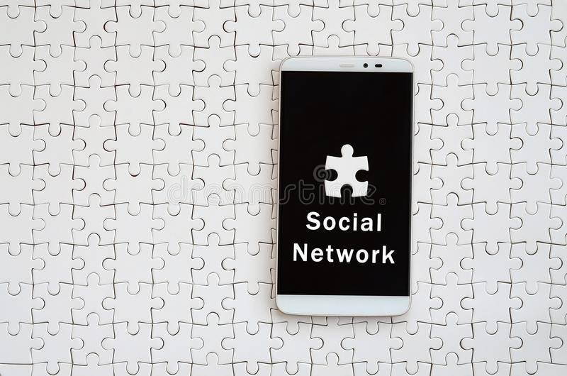 A modern big smartphone with a touch screen lies on a white jigs. Aw puzzle in an assembled state with inscription. Social network royalty free stock photos