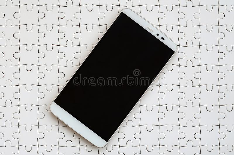 A modern big smartphone with a touch screen lies on a white jigsaw puzzle in an assembled state.  royalty free stock photo