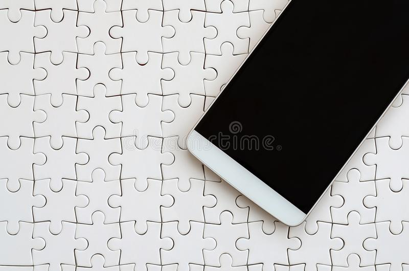 A modern big smartphone with a touch screen lies on a white jigsaw puzzle in an assembled state.  stock image