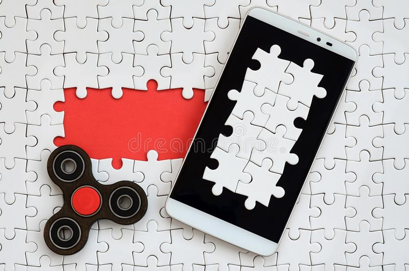 A modern big smartphone with a touch screen and a spinner lie on a white jigsaw puzzle in an assembled state with missing elements.  stock images