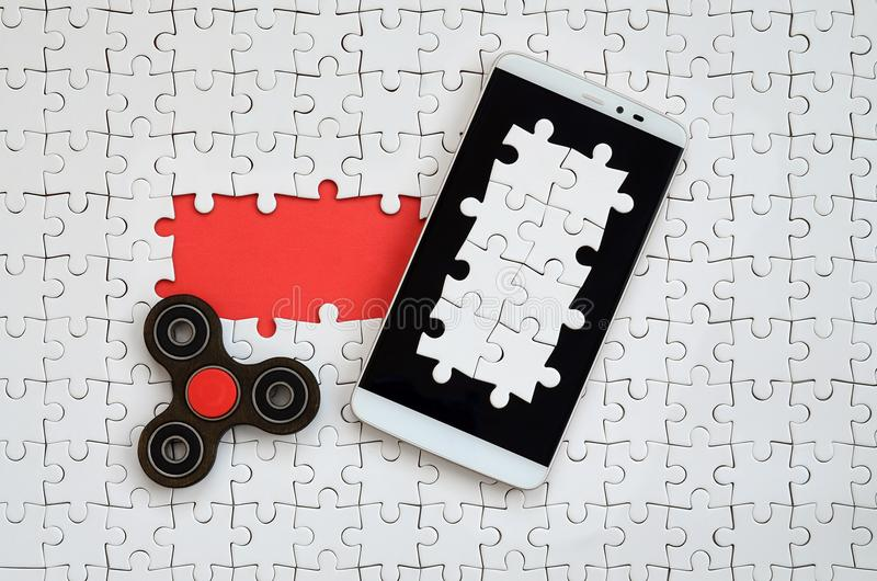 A modern big smartphone with a touch screen and a spinner lie on a white jigsaw puzzle in an assembled state with missing elements.  stock image