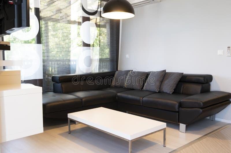 Modern binnenland van woonkamer met comfortabele zwarte leerbank royalty-vrije stock foto