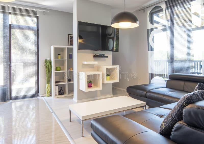 Modern binnenland van woonkamer met comfortabele zwarte leerbank royalty-vrije stock afbeelding