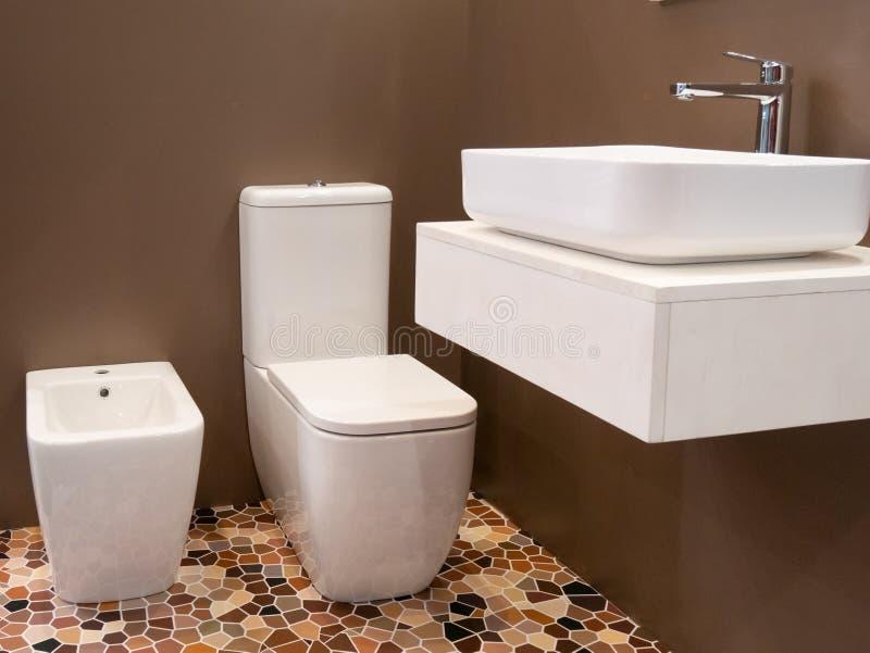 Modern binnenlands ontwerp van hotelbadkamers met wasbak, toilet en bidet stock afbeelding
