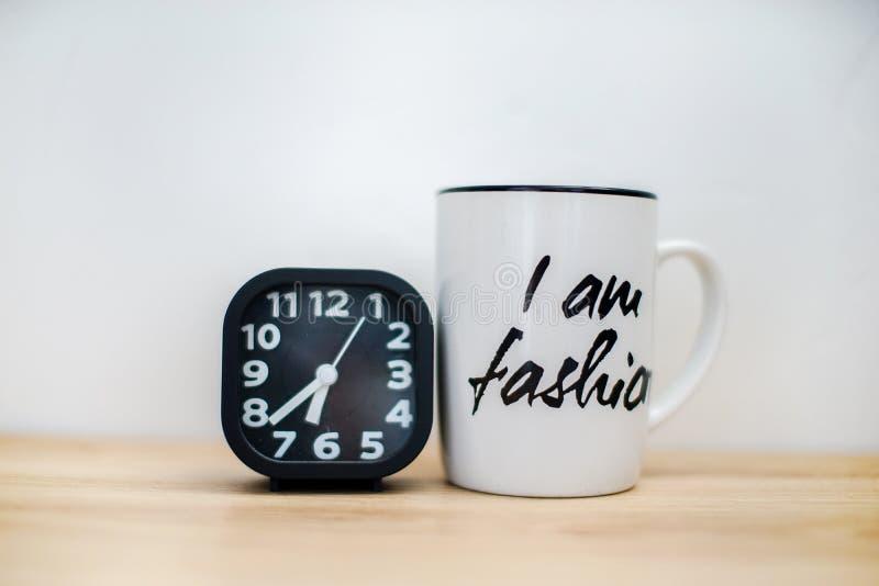 Modern black alarm clock next to coffee mug stock images