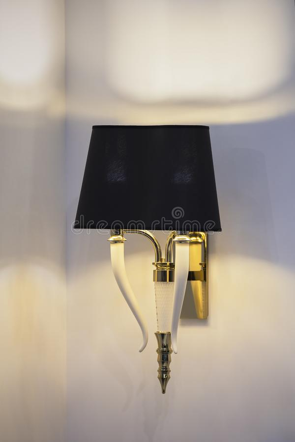 Modern black wall lamp with white fangs. Beautiful decor of a fashionable chandelier.  stock photo
