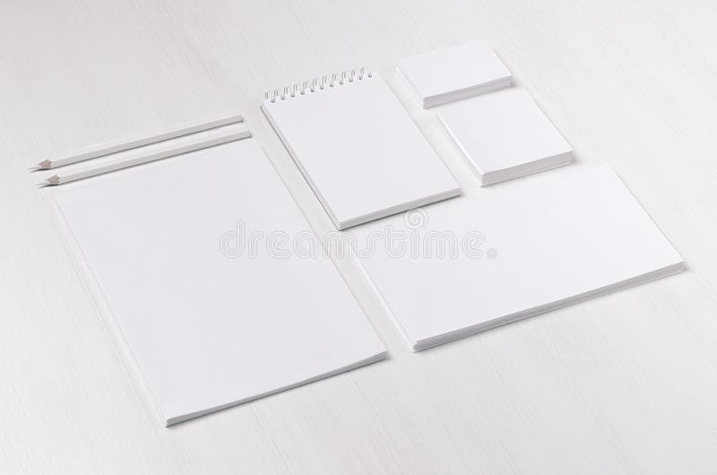 Modern blank white business stationery set with card, label, paper, notepad on soft light white wood table, inclined. Modern blank white business stationery set royalty free stock photography