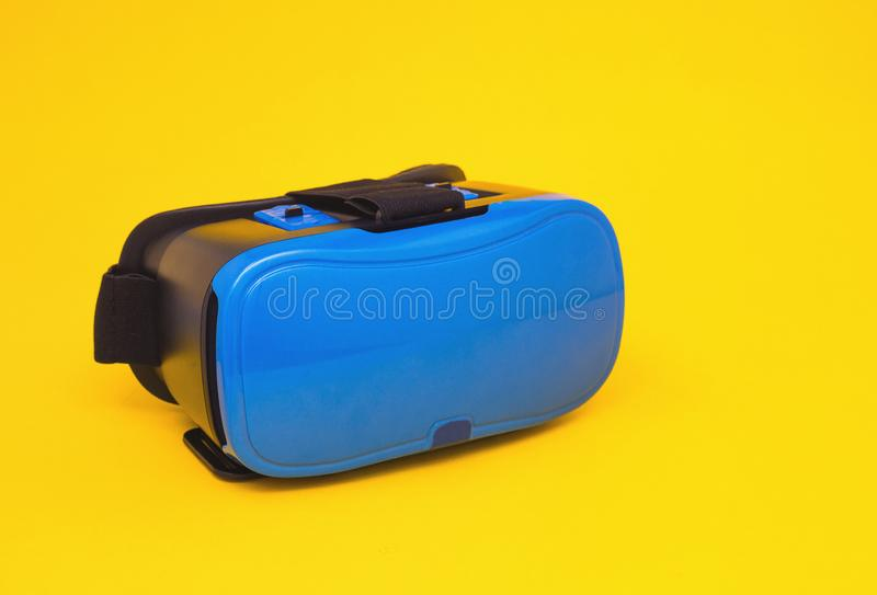 Modern blue glasses of virtual reality for smartphone and phone on yellow background, close-up, multimedia, video game royalty free stock images