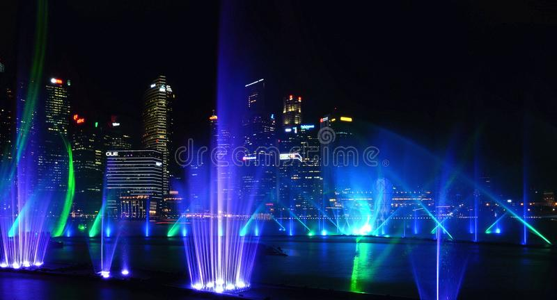 Modern blue green fountain show on sea and abstract architectures and night skyline in Singapore stock photos