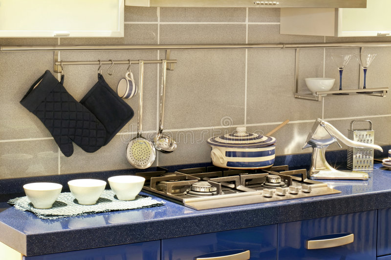 Modern blue kitchen counter. Contemporary blue kitchen counter and integrated hob with cooking utensils stock images