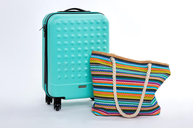 Modern blue suitcase, beach handbag. stock photo