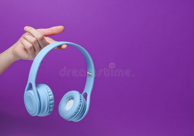Modern blue wireless headphones. On finger of female hand on a purple background. Copy space stock images