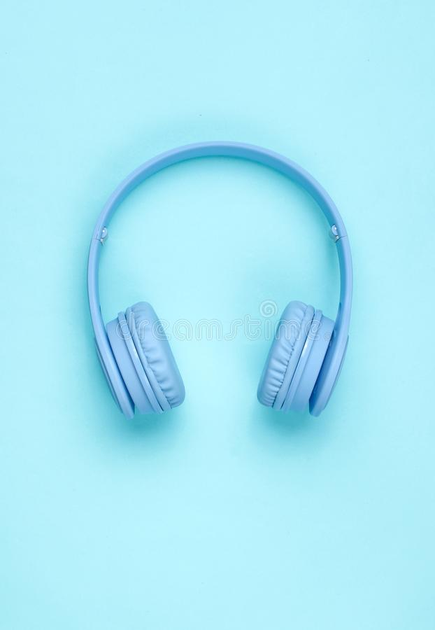 Modern Blue Wireless Over-Ear Headphones. On blue pastel background. Minimalism. Top view stock image