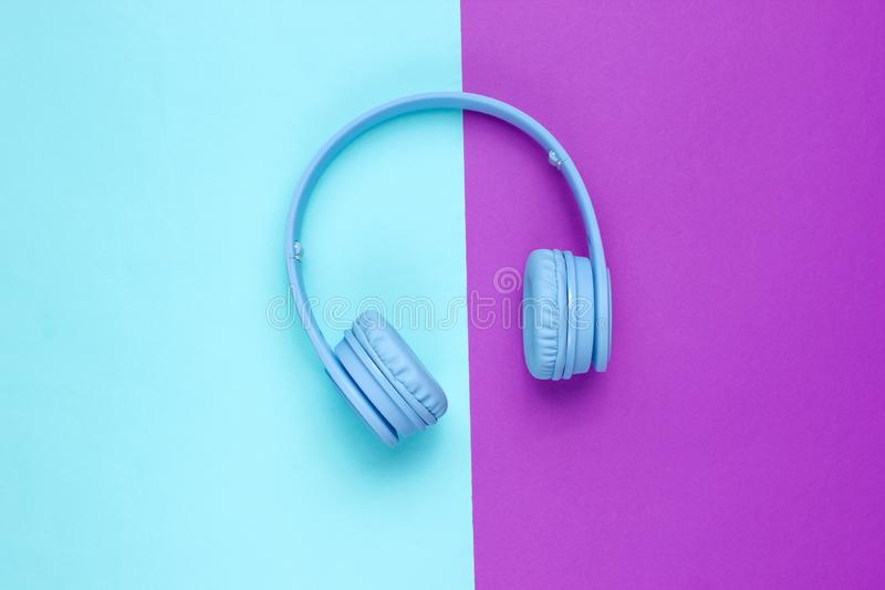 Modern Blue Wireless Over-Ear Headphones. On a blue-purple background. Minimalism. Top view royalty free stock photography