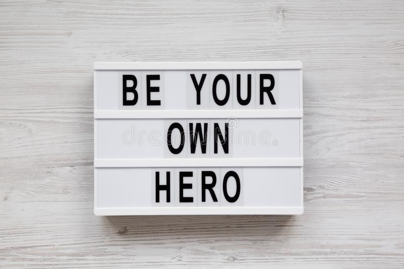 Modern board with text `Be your own hero` on a white wooden background, top view. Flat lay, overhead, from above. Close-up stock photography