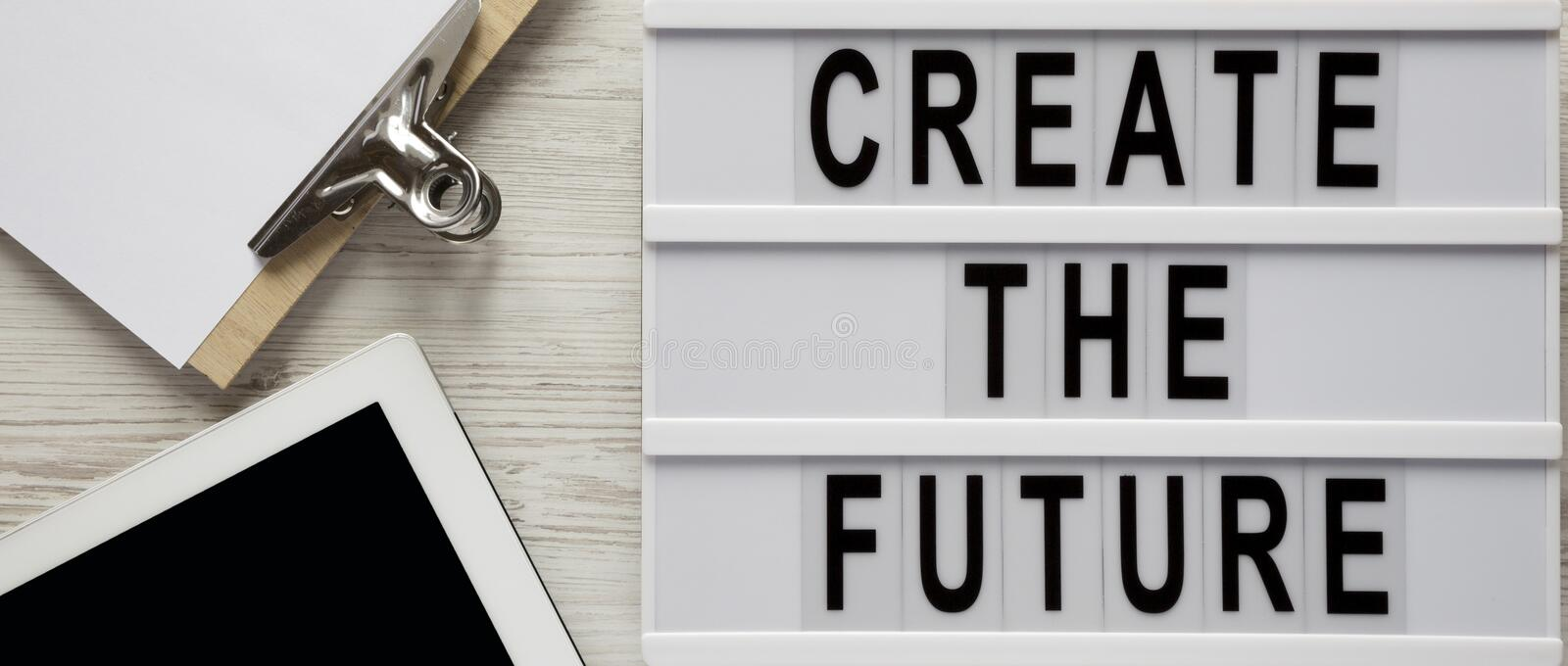 Modern board with text `Create the future`, clipboard with sheet of paper, tablet on a white wooden table, top view. From above, stock photos