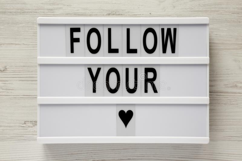 Modern board with text `Follow you heart` over white wooden background. Close-up stock image