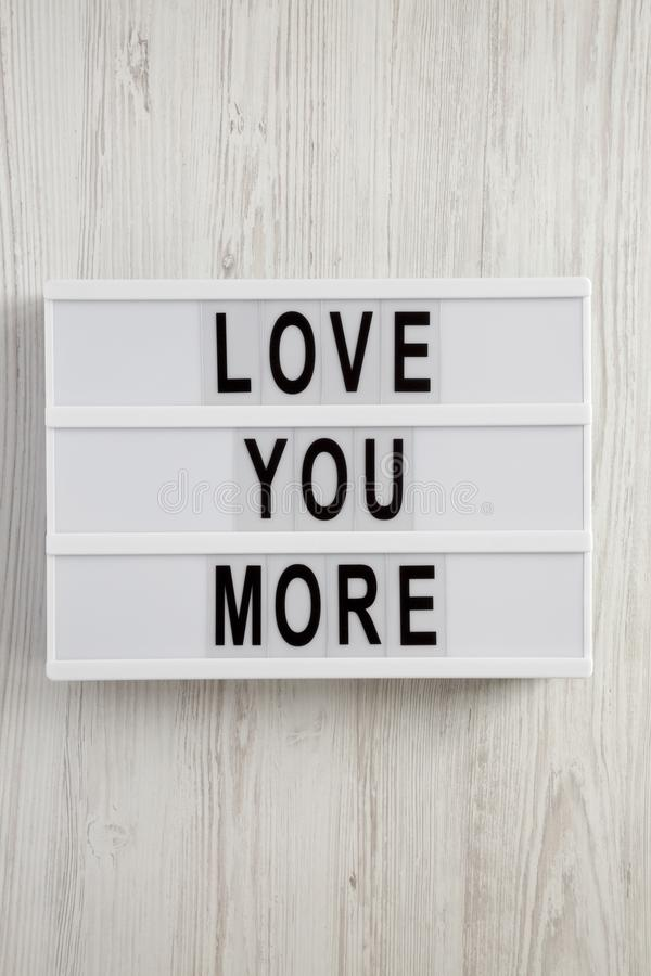 Modern board with text `Love you more` on a white wooden background. Valentine`s Day 14 February stock photography