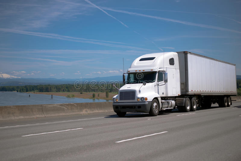 Modern bonnet white big rig semi truck with semi trailer driving. Modern bonnet classic white big rig semi truck with dry van semi trailer – traditional stock images