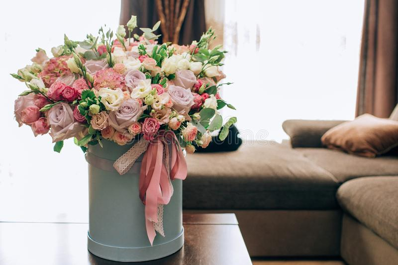 Modern bouquet of flowers in blue round box on a wooden table. Beautiful floral arrangement in a hat box. Flowers bouquet in stock photography