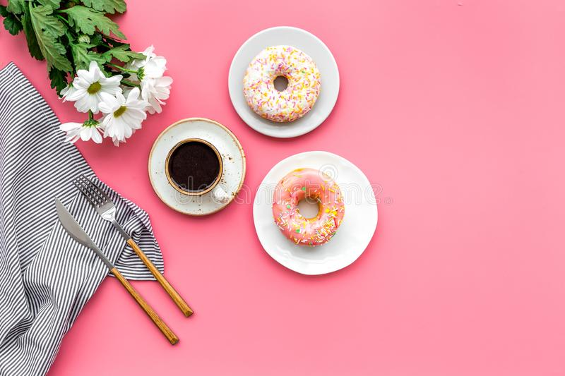Modern breakfast desing with sweet donut, coffee and flowers on woman pink desk background top view mock up royalty free stock image