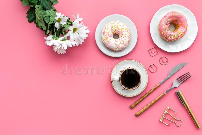 Modern breakfast desing with sweet donut, coffee and flowers on woman pink desk background top view mock up stock photo