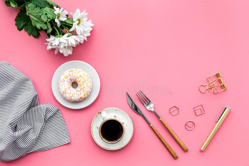 Modern breakfast desing with sweet donut, coffee and flowers on woman pink desk background top view mock up royalty free stock photos
