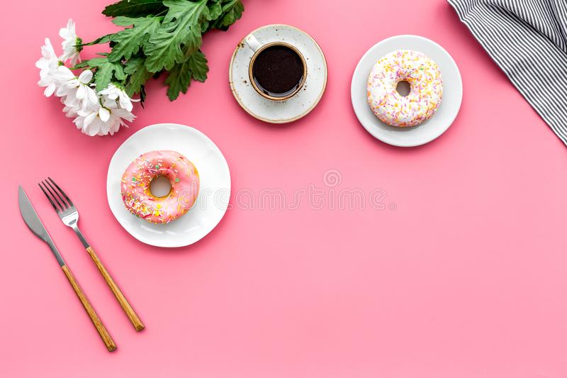 Modern breakfast desing with sweet donut, coffee and flowers on woman pink desk background top view mock up royalty free stock photo